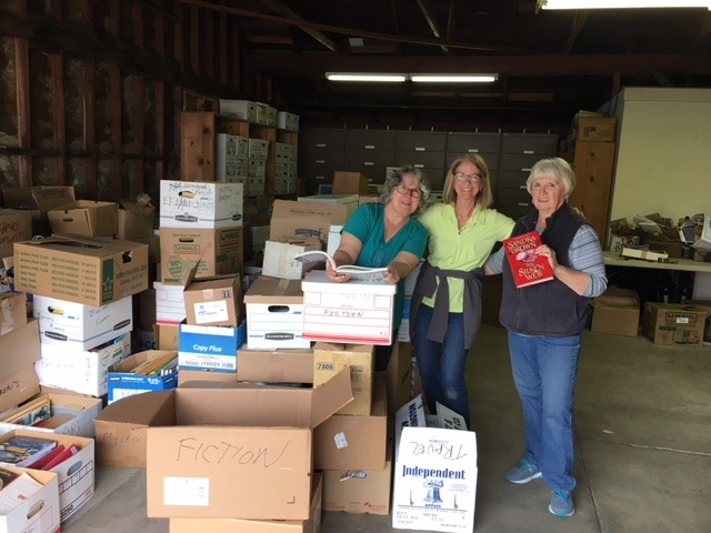 Maree Hawkins, Cathy Peck, and Pat Glatkke sorted thousands of donated books by genre in the months before the 2017 sale.