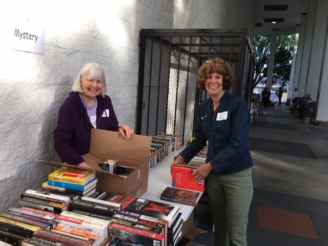 Carmen Pedrioli and Jean Haven set out mystery books before the sale opened at 8:00 am.