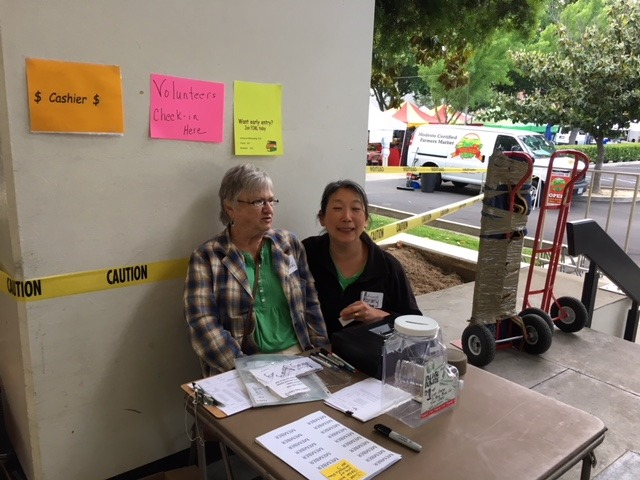 Volunteers Claudia Sargent and Lin-Ching Malone are ready for the sale to begin.