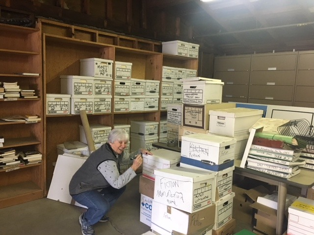 Pat Glatkke marks boxes of sorted books in the warehouse.