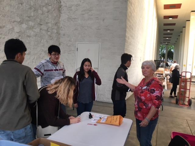 Teen volunteers check in with coordinator Pat Glattke.