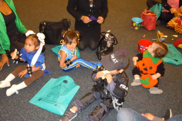 costumed children eating cookies after Halloween parade