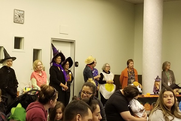 The Friends organized a parade around the library following Halloween Story Time. Volunteers, from left to right at back of room were Carmen Pedrioli, Christine Brereton, Cande Brody, Pam Pallios, Jean Haven, Anne Britton, Maree Hawkins, and Beverly Schlegel.