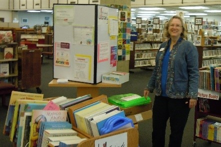 Anne Britton stands beside books to be given away during Dia event
