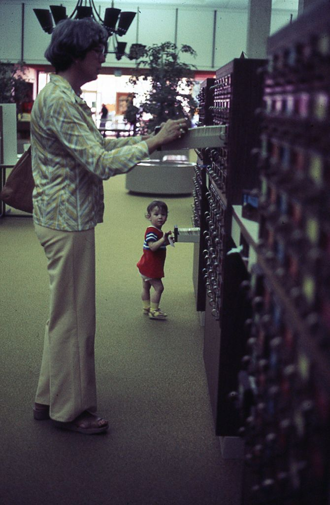woman and toddler standing at open card catalog drawers