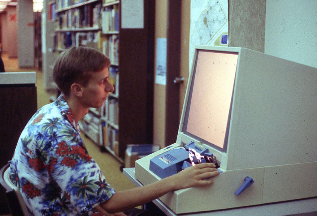 man seated at microform machine